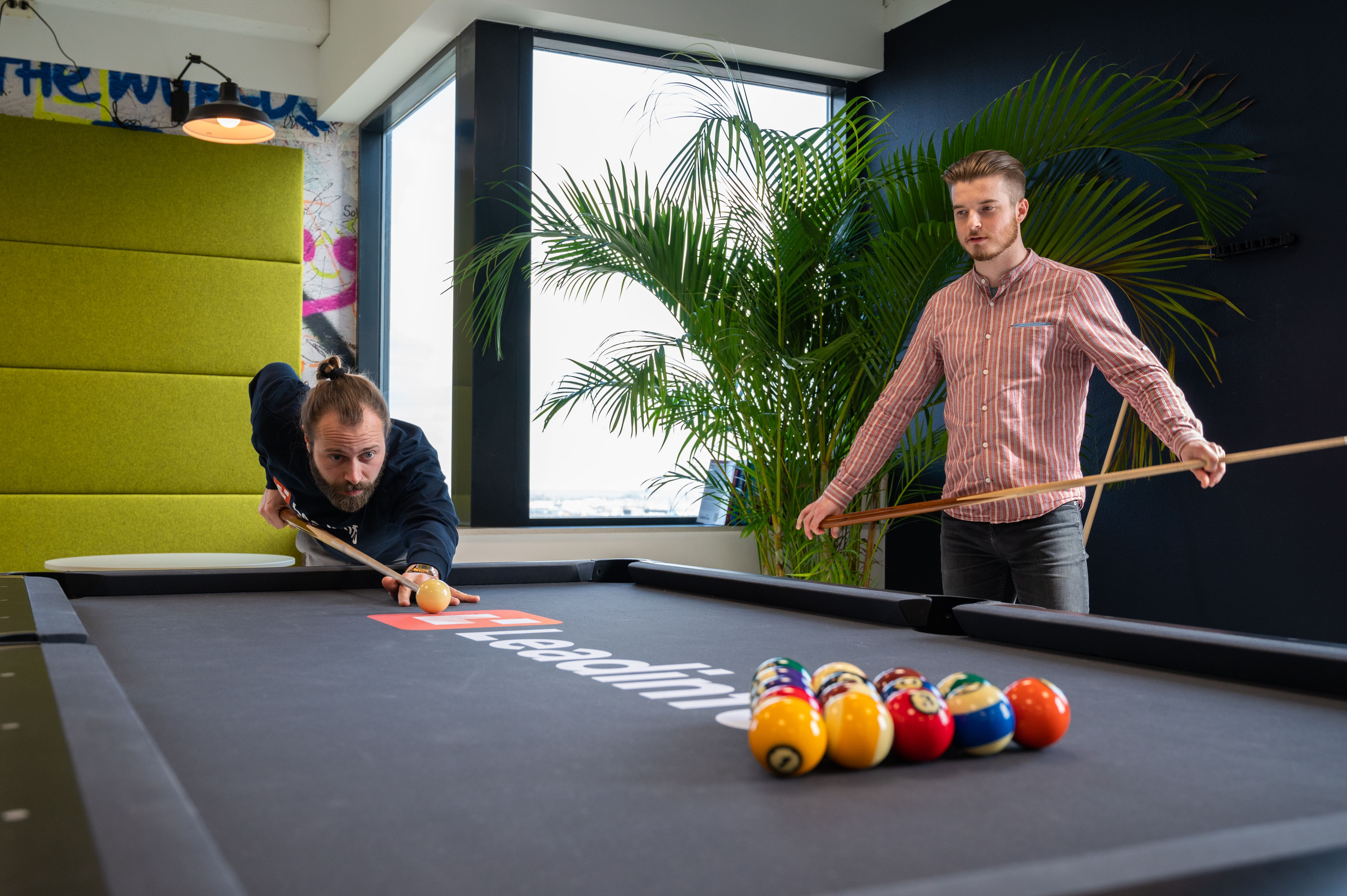 Two leadinfo employees playing pool